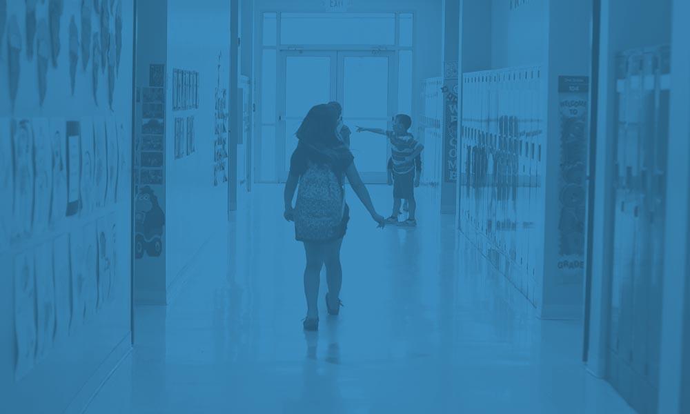 Young Girl Walking Through A School Hallway